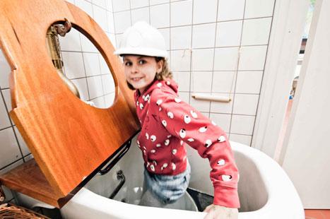 Lille pige med sikkerhedshjelm på vej ned i toilet