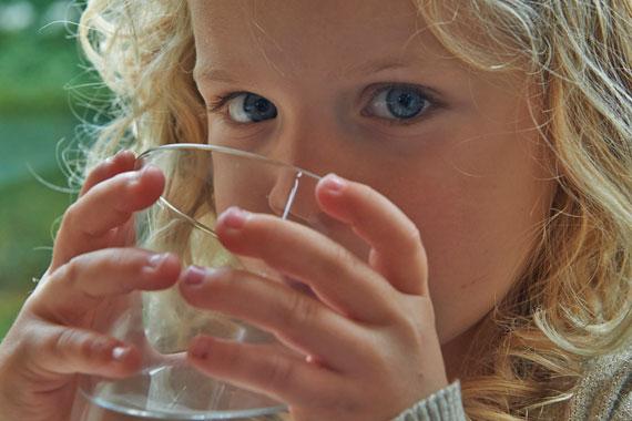 En pige drikker et glas vand